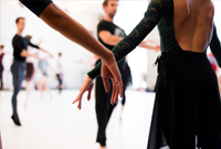 A close up photo of two dancers arms with other dancers in the background taken during a rehearsal in a ballet studio