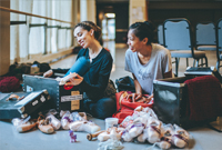 Photo of Jordana Daumec and Jenna Savella packing their pointe shoes into a travelling container