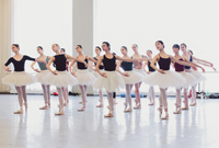 A photo of the female dancers in the corps de ballet in rehearsal in a ballet studio