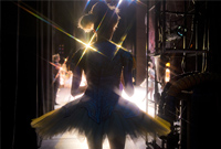 Accompanying photo of a dancer in a tutu seen from behind as she stands in the wings looking onto the stage