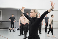 Choreographer Crystal Pite leading the dancers in rehearsal in a ballet studio