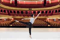 A photo of Principal Dancer Guillaume Cote on stage in Paris with a view to the empty auditorium
